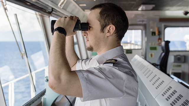 Captain looking out of his ship using a pair of binoculars