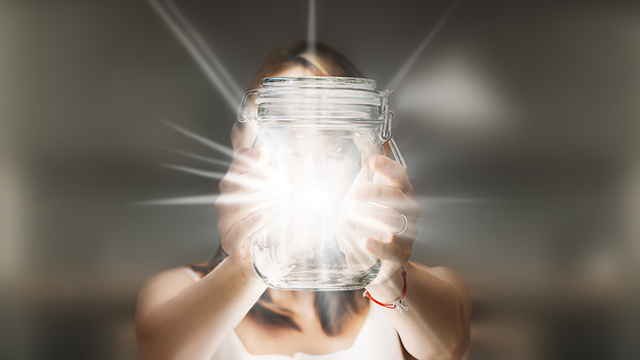 woman holding glowing glass jar 640x360