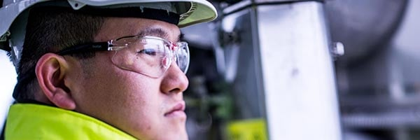 asian oil refinery worker seen in profile
