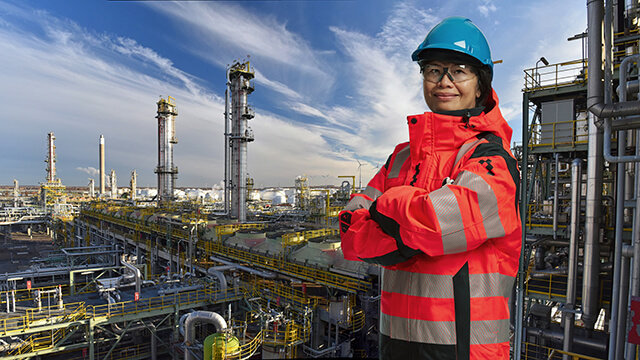 female asian engineer infront of refinery
