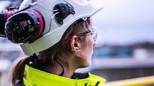 Female oil refinery worker gazing