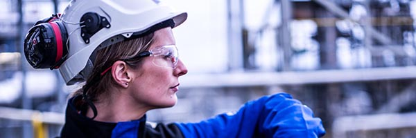 female oil refinery worker leaning on railing