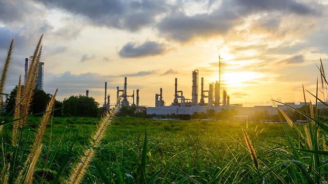 oil-refinery-green-grass-plants-sunset