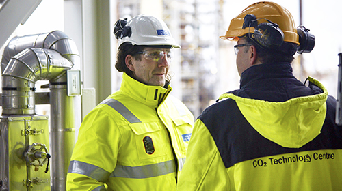 workers discussing at oil refinery