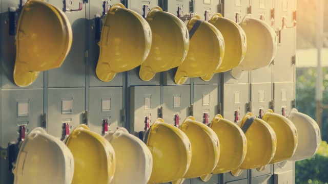 Several yellow helmets hanging on a wall