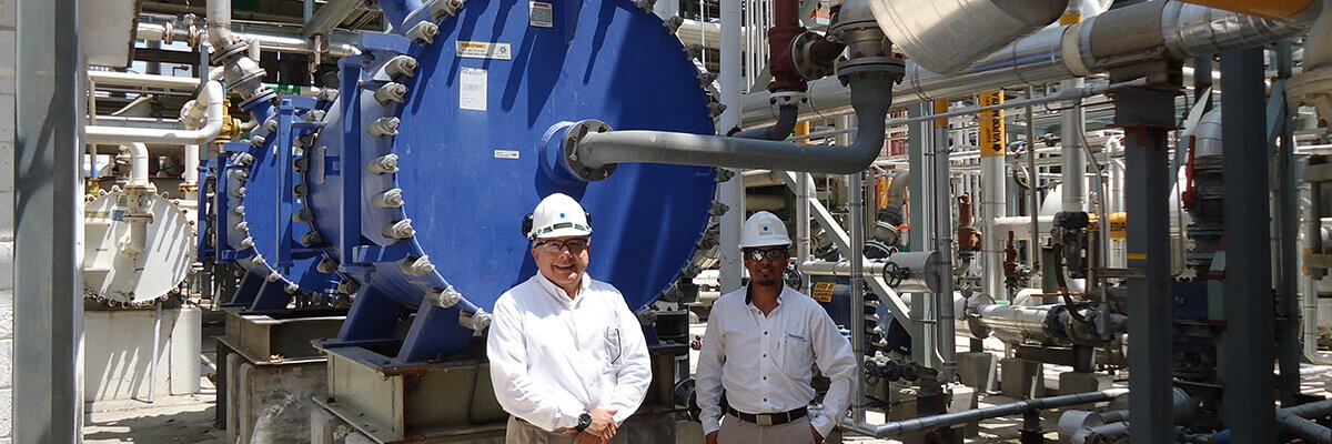 two men standing in front of a spiral heat exchanger installation