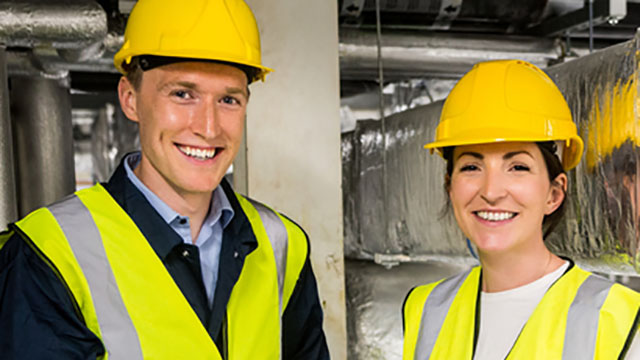 Man and Woman with safety gear on, smiling