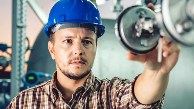 Man with hard hat inspecting machinery
