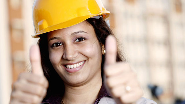 Smiling woman wearing a hard hat and giving two thumbs up