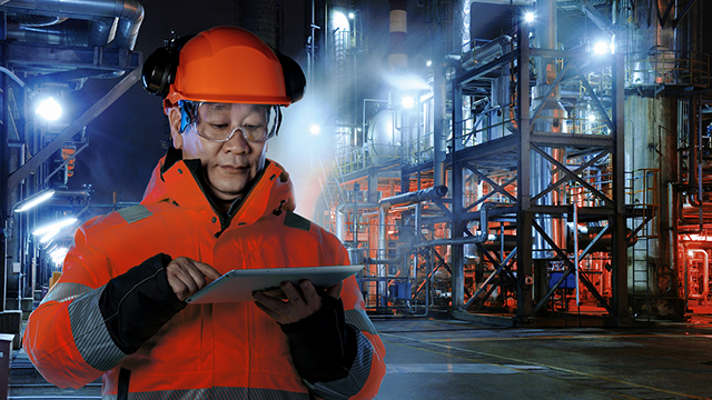 male Asian engineer wearing hard hat and safety glasses holding ipad infront of industrial plant