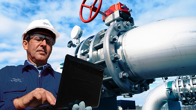 engineer wearing hard hat and safety glasses holding laptop in front of pipes and blue sky