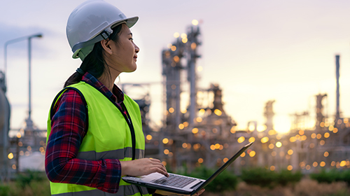 Female engineer with laptop outside chemical plant