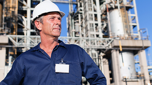 male engineer gazing infront of petrochemical plant
