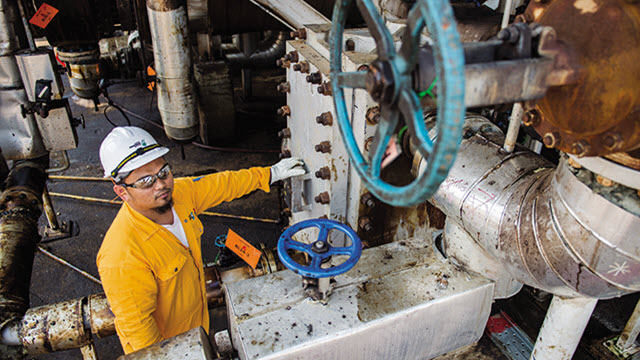 Asian oil refinery worker infront of an installed Alfa Laval Compabloc welded plate heat exchanger