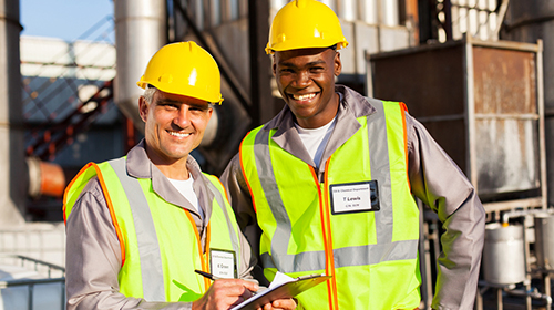Two smiling engineers outside chemical plant