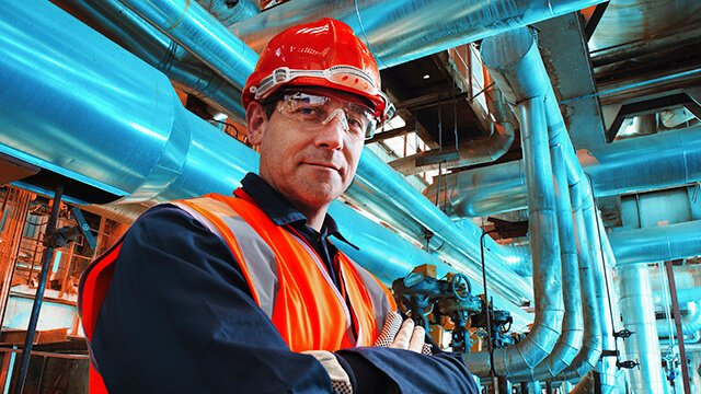 Engineer in front of blue industrial pipes