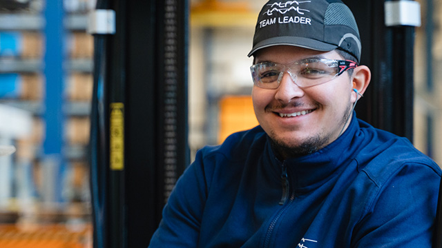 Smiling man in workshop wearing team leader cap and safety glasses