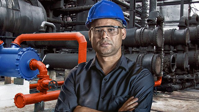 Man wearing hard hat and safety glasses with crossed arms infront of an installed Alfa Laval welded spiral heat exchanger.