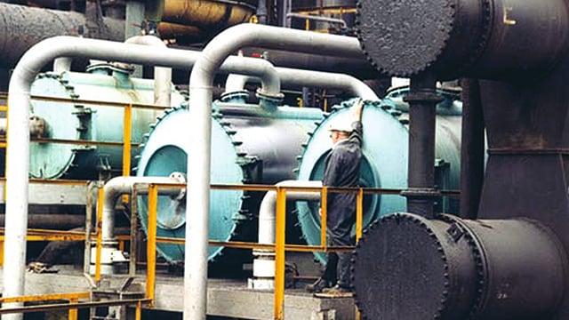 Man infront of three installed Alfa Laval welded spiral heat exchangers