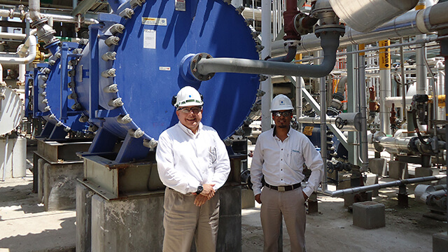 Happy customers at Mexichem in front of an installed Alfa Laval spiral heat exchanger
