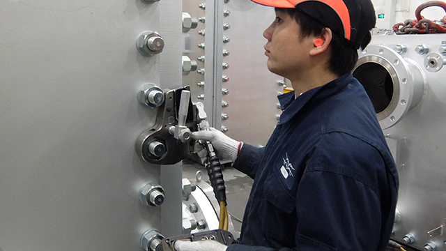 asian man inspecting compabloc welded plate heat exchanger