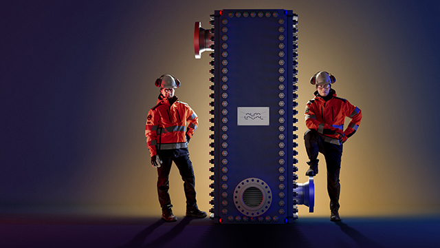 Male and female engineers standing next to Alfa Laval Compabloc welded heat exchanger