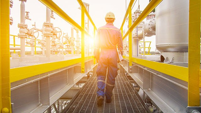 Engineer wearing hard hat seen from behind walking into the setting sun at industrial plant