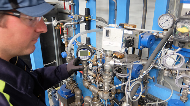 Man checking control system for Alfa Laval Compabloc welded plate heat exchanger