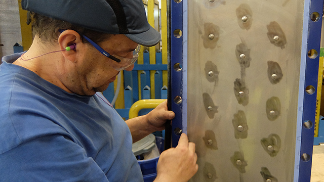 Man checking panel gaskets on Alfa Laval Compabloc welded plate heat exchanger