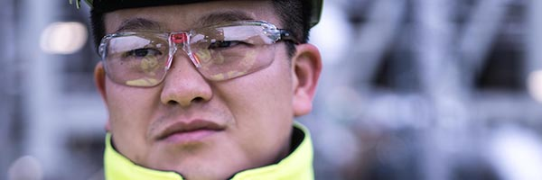 Close up of male Asian engieer wearing hard hat and safety glasses