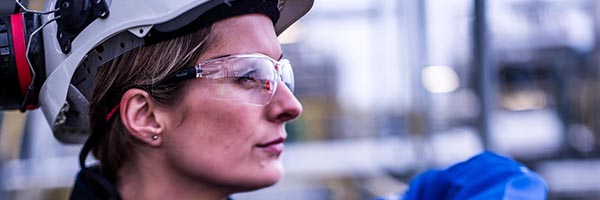 Female engineer wearing hard hat and safety glasses seen in profile